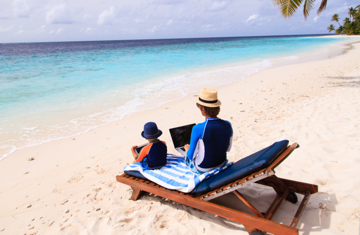 family with laptop and touch pad at beach